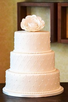 Quilted and beaded traditional ivory wedding cake with a handmade Ranunculas flower