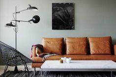 Styling: Pella Hedeby. Gray walls, tan leather couch. Living room