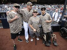 Game #17, 4/22/2012: Mark Kotsay #14 of the San Diego Padres poses with a group of wounded Marines as part of Military Opening Day before a baseball game against the Philadelphia Phillies at Petco Park on April 22, 2012 in San Diego, California. (Photo by Denis Poroy/Getty Images)