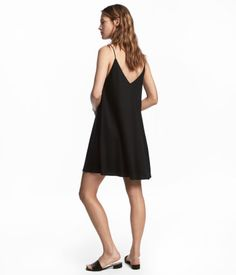 Black. Short jersey dress. Narrow shoulder straps, V-neck at front and back, and double layers of fabric at top.