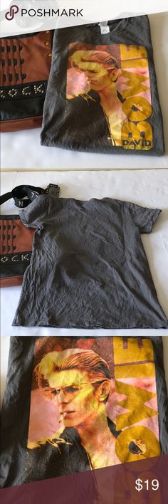 David Bowie Graphic Tee Showcase your love for the late David Bowie with this ultra cool gray short sleeve graphic tee. Bowie logo on front with a solid gray back. Logo is intentionally distressed with only adds to this terrific tee. In excellent pre loved condition. Size medium. Fabric Content: 100% cotton. Bundle for biggest savings! Gildan Tops Tees - Short Sleeve