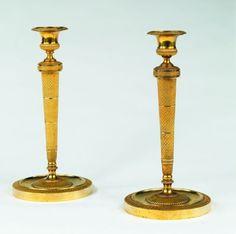 Paire de bougeoirs en bronze ciselé et doré, le binet en forme de vase, le fut décoré de losanges. Ils reposent sur des bases cylindriques à godrons et palmettes. Epoque Empire.
