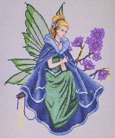 A pretty picture of a fairy in blue and green with a spray of mauve flowers.