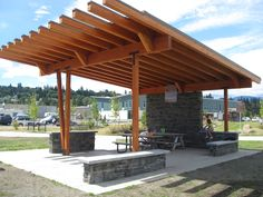 Designed to be nearly horizontally transparent, these stone and wood shelters at Hood River Park consist of a horizontal roof plane supported on one side by a stone wall and on the other by wood columns. The stone wall steps down to counter top height to provide food preparation and serving surfaces and then steps down again to provide seating.  Utilizing the landscape wind breaks allowed Boxwood to keep the shelter open and bright. #park #picnic #Oregon #architecture #design #Boxwood