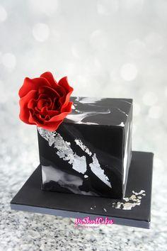 A Black Marbled birthday cake with silver leaf