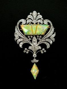 An early 20th century Belle Epoque  diamond & opal set brooch, designed as a three panel opal centre within old cut diamond set openwork scroll border, all supporting opal drop, all claw, collet & pave set in yellow & white metal, the reverse with detachable brooch fitting.