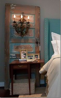 This bedside decor gets an A+ for creativity.  I love the juxtaposition of the nailhead bold turquoise headboard with the shabby door and sconce.