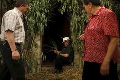 """A man makes a """"cachiporra"""" (a traditional whip made of grass) as he sits in a decorated doorway during Corpus Christi day in El Gastor, southern Spain, June 7, 2015. REUTERS/Jon Nazca"""