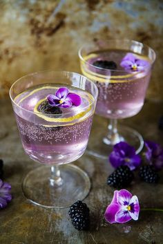 Blackberry French 75's½ cup water ½ cup sugar ¼ cup fresh blackberries 1 oz Gin 1 tablespoon fresh Lemon juice 2 oz Champagne fresh blackberries and lemon rind for garnish