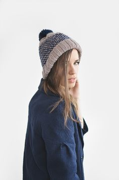 Hand knitted unisex hat with fluffy handmade pom pom.  *YARN:* Wool blend.  *COLORS:* Here shown in lavender grey (main colour) and dark blue (pattern & pom pom). You can choose any of the...