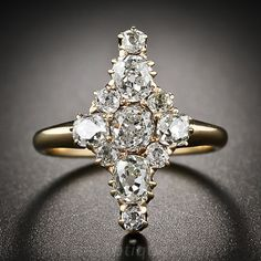 A darling and dazzling diamond dinner ring, dating from the mid-to-latter-nineteenth century, is ablaze with eleven high-crowned old mine cushion-cut diamonds, totaling 1.50 carats, arrayed in a stylized navette shape. An original Victorian beauty measuring 3/4 inch high.