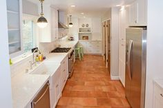 White cabinets and white marble countertops contrast nicely against terracotta colored floor tiles in this Piedmont kitchen remodel. Kitchen designed by: Drafting Cafe www.draftingcafe.com