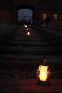 Candles left by visitors on the rails inside the Auschwitz II-Birkenau camp