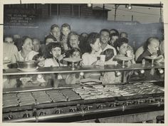 Photograph showing a hungry crowd eating and drinking at Nathan's food counter on Coney Island with hot dogs and rolls cooking on the grill, 1947