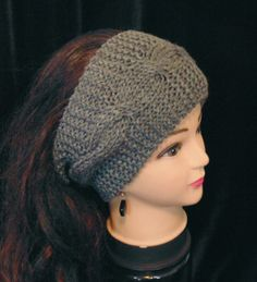 This woman's headband ear warmer is handmade in knitted braided cable stitch. The color is a charcoal grey. It's wide and covers most of the head.  Color: Charcoal Grey Material: 100 % soft acrylic yarn Size: Adult / Teen Machine Wash - Washing and Care instructions sent with every item