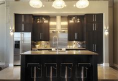 Love the dark wood cabinets. Would love to know the maker and finish on the cabinets.