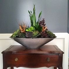 This beautiful succulent arrangement is designed using high quality permanent botanicals. The silver oval boat planter is crafted with lightweight aluminum product. This piece is non-scented, hypoallergenic and therefore perfect for public places, hospitals, rest homes and the