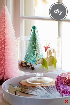 """Transform a simple trifle dish and tray into a mini holiday environment. Hand-painted animals from Hand Made Modern(an easy DIY), slices of wood and faux snow adda natural feel, while a mercury-glass tree and lit votive candlehelp create an elegant, soft glow. Elevating the trifle dish on aslice of wood gives balance your """"winter scene"""" and lets youuse it as a centerpiece, or pop it in front of a window, on acoffee table or a side table."""