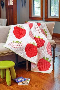 Nothing says summer quilts like strawberries! Use an assortment of red prints to create the big strawberry blocks for this throw quilt pattern called Strawberry Fields, by Liz and Elizabeth Evans. This quilt is featured in Episode 2712 of the Love of Quilting TV show. #LoveOfQuilting