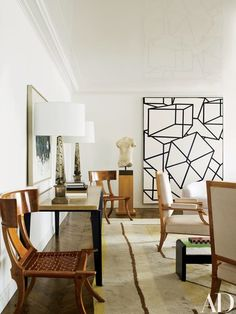 Klismos chairs by T. H. Robsjohn-Gibbings flank a Jean Prouvé table in the living room; the sycamore armchairs are by André Arbus. The Roman torso is second century, and the painting at right is Phoenicia VIII by Al Held | archdigest.com