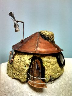 Steampunk Fairy House - painted papercrete house, tuna can roof & door, pop can windmill, hammered copper pipe porch, hardware cloth railing, and miscellaneous found objects for the windows.