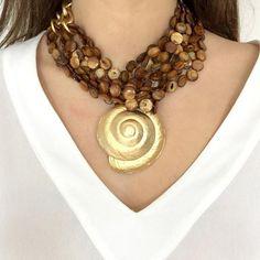 Collar largo de nacar en colores unidos por eslabones de cadena de latón bañados en oro mate y adornado por concha de mar de latón bañada en oro mate. La longit