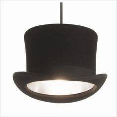 Una lámpara de suspensión para quitarse el sombrero. Su diseñador, de origen inglés, ha convertido un modelo de sombrero que fue un icono cultural, en un elemento de iluminación que recuerda a tiempos pasados de la sociedad británica. Tiene la forma exacta del auténtico sombrero de copa, pero revestido en su interior de aluminio para aumentar la reflexión de la luz.