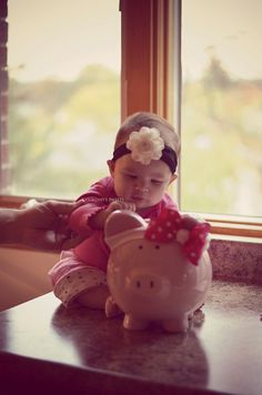 A baby and her piggy.  Child to Cherish, Big Ear Piggy Bank. #childtocherish