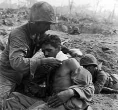 A U.S medic applies a field dressing to the neck of an injured soldier in Tanapag, Saipan in June 1944. In the distance behind them, a soldier is visible in a foxhole.