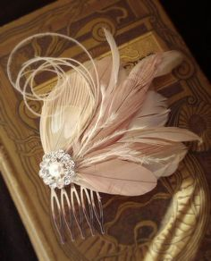 Goose & ostrich feathers. Ivory pearl and rhinestone button! Purrdy!