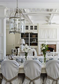 view from the kitchen: lantern chandelier, brick fireplace, white woodwork details