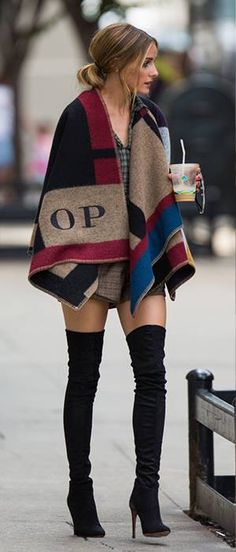 Olivia Palermo pairs her Stuart Weitzman boots with a monogrammed Burberry cape. Those boots!!!