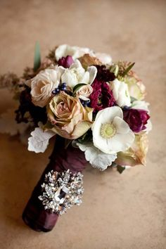 The bridesmaids bouquets will be clutches of beige roses, burgundy ranunculus, blush spray roses, burgundy scabiosa flowers, gold seeded eucalyptus, white wax flowers, and brown scabiosa pods wrapped in burgundy ribbon all the way down.