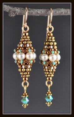 These earrings are made using a right angle weave to create a bead out of beads. They are made with Swarovski 4mm cream colored pearls and Japanese seed beads and hang from gold filled earring wires, strung with heishi and has a 3mm Swarovski Turquiose ab2x tassel.
