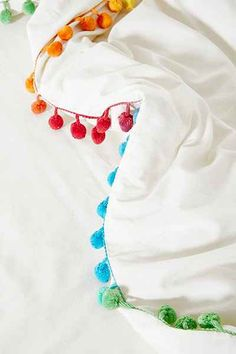 rainbow pom pom trim. love! Taking my bedskirt to the seamstress to do this