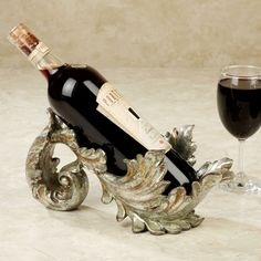 Display your favorite vintage in the supremely elegant Frazier Baroque Gold Acanthus Leaf Wine Bottle Holder. Shaped like an open scrolling acanthus leaf, the resin holder is hand-finished in regal baroque gold with blush overtones. Wine Bottle Holders, Bottle Stoppers, Bottle Openers, Wine Carafe, Wine Bottles, Wine Glass, Red Kitchen Accessories, Wine Shelves, Wine Baskets
