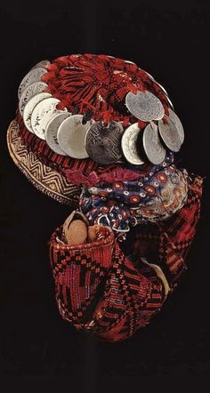 Traditional headdress from the Hebron Hills (West Bank, Palestine). Called 'aragiyeh'. Ca. mid-20th century. Embroidered in cross-stitch; embroidered hairbands 'laffayef' of cotton 'dendeki' are bundled at the back; coins Maria Theresa dollars 'abu risheh' and Turkish coins. The embroidered edge of the undercap 'taqiyeh' projects from the edge.   (©British Museum).