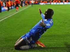 Demba Ba: Slides towards the Chelsea fans in celebration