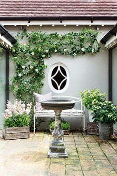 Small back garden with climbing trellis, stone font and outdoor bench.