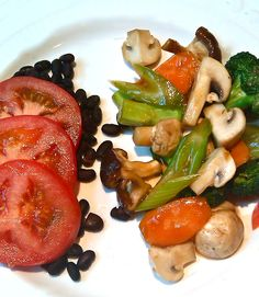 Veggie stir fly with mushroom sauce and tomatoes over black beans. Simple, fast, easy. (No oil.)