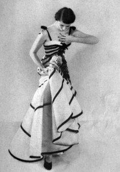 người mẫu của Báo Vogue Paris vào năm 1950. Người phụ nữ này đang mặc trang phục của nhà thiết kế nổi tiếng o Pari - Christian Dior.với kiểu váy có phần thân áo là cúp ngực khoe duoc vong 1 khiến ng mẫu trong sexy nhưng k kém phần quí phái.