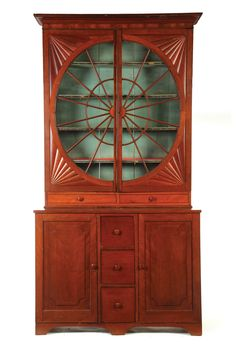 """UNUSUAL LIBRARY BOOKCASE.  Possibly Ohio, 1825-1850, cherry and poplar. Two-piece, the upper section is a bookcase with unusual glazed doors, the lower section has three drawers flanked by two doors. Imperfections. 107""""h. 54""""w. 19""""d."""