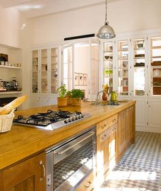 Check cement tiles, long oak island, and double-sided glass cabinets for unobstructed light; Nuevo Estilo