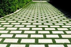 A Palm Beach home has a driveway made of pavers with grass joints.