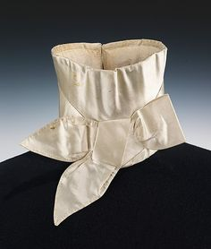 Wedding stock, American, 1835. Silk, metal. This is an elegant example of a stock, the standard neckwear for men in the early 19th century, to be worn over the high stand collar of the shirt. The crisp and complete stock with a tailored bow was essential in fashionable formal dress.