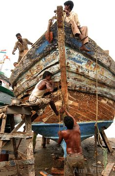 Fishing families in Nagapattinum district in Tamil Nadu, India repairs boat