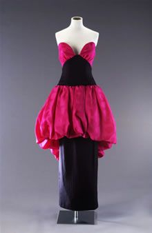 Black and fuschia silk-blend satin and cotton-blend velvet evening dress by Bruce Oldfield, British, mid-to-late 1980's. Strapless evening dress with plunging wide V-shaped bodice, narrow sheath-like long skirt and puffball overskirt (to just above the knees at the front, and dipping down to just below the knees at the back), made of black and bright fuschia pink satin-weave silk mix fabric.