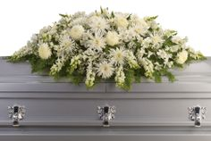 This exquisite casket spray of artistically arranged white flowers is like a blanket of love and caring. It is a very personal farewell to someone who will be deeply missed.