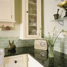 Subtle green of the tiles takes lifts the flat black and white/ cream scheme.