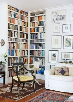 chic library or living room with white walls and white slip covered sofa and art wall